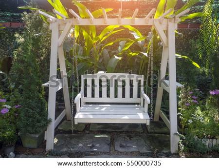 White Wooden Porch Swing In Garden