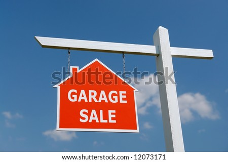 White wooden post with red Garage Sale notice board over blue sky - stock photo