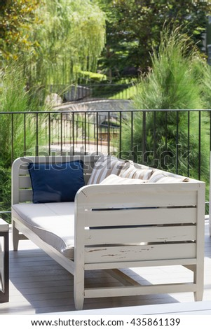 White wooden sofa with pillow and garden in background for relax time