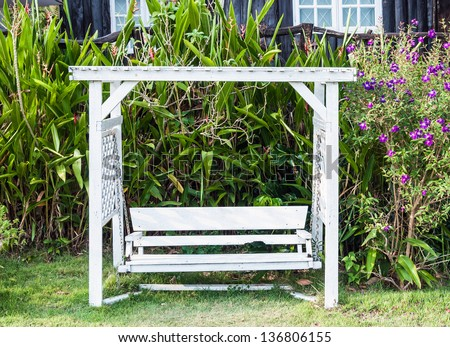 White wooden swing in the garden of country house - stock photo
