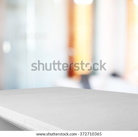 White wooden table on blurred interior background - stock photo