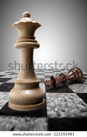 White wooden victorious queen standing on a chessboard against the background of a crushed defeated king. - stock photo