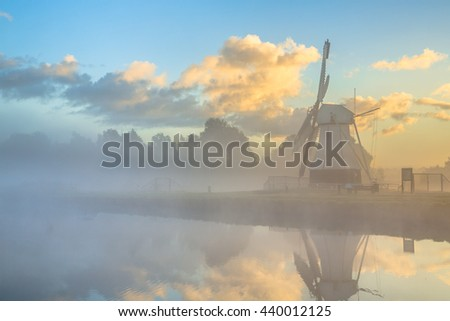 White wooden windmill at river in morning fog during sunrise, Drenthe, Netherlands - stock photo