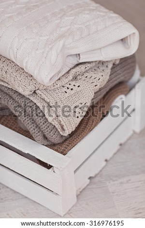 White wool sweaters in wood box on white wood floor - stock photo