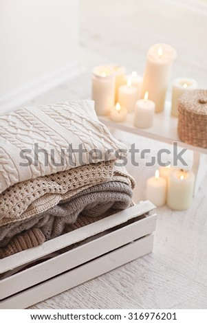 White wool sweaters in wood box on white wood floor and candle - stock photo
