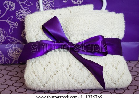 White woolen hand-knit children plaid with hearts bent and tied with a purple bow, close-up - stock photo