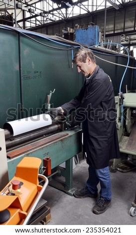 White worker prepare a piece of material with a manual machine. Construction of a homemade muffler for sportive cars in stainless steel.