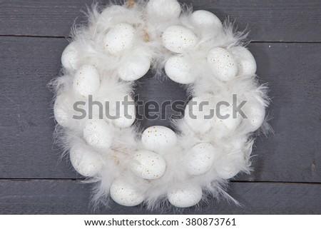 White wreath with white eggs on dark wooden background - stock photo