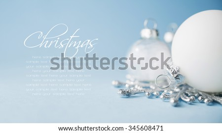 White xmas ornaments on light blue background. Merry christmas card. Winter holiday theme. Space for text. Happy New Year. - stock photo