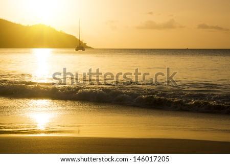 White yacht near rocky coast of seychelles. Gold sunset on sand beach - stock photo