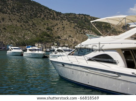 White yachts on blue water standing in harbour, recorded in place Balaklava in Crimea on Black sea.