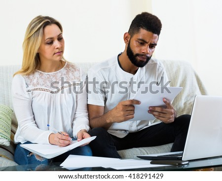 White young woman and black man with documents at home