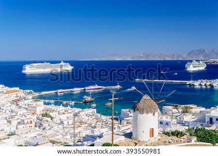 Whitewashed city of Mykonos and a famous greek windmill with cruise ships in the distance, Mykonos island, Cyclades archipelago, Greece - stock photo