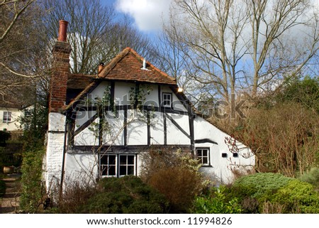 Whitewashed timbered cottage in a woodland setting somewhat reminiscent of an enchanted fairytale scene from childhood - stock photo