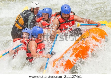 WHITEWATER RAFTING TEAM IN BRIGHT SUNLIGHT INFLATABLE BOAT