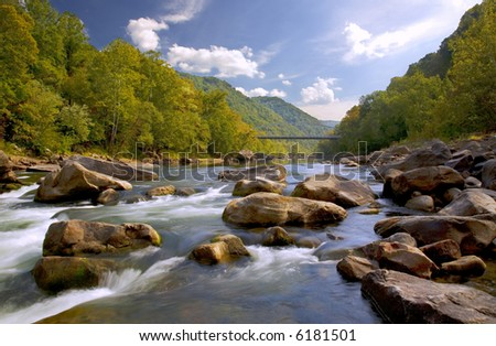 Whitewater River with Bridge, Trees and Cloud Filled Sky - stock photo