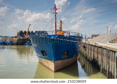 Whitstable, UK -  August 7, 2014: Pluto, a large moored cargo ship preparing for the local Harbour Day dominates the marina in Whitstable.