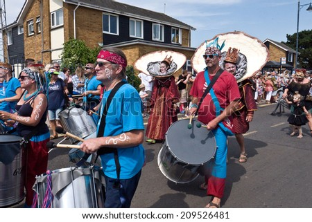 WHITSTABLE, UK-JULY 26: The Samba Pelo Mar band takes part in the annual Whitstable Oyster Festival Parade, watched by thousands of visitors. July 26, 2014 Whitstable UK. - stock photo