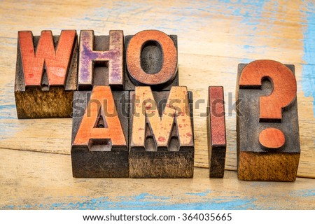 Who am I - a philosophical question spelled in vintage letterpress wood type printing blocks against grunge, painted wood - stock photo