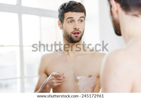 Who am I? Frustrated young shirtless man pointing himself while standing against a mirror  - stock photo