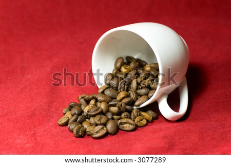 Who spilled the beans? A cup of coffee beans tipped over on a textured red background - stock photo