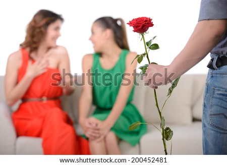 Who to choose? A young man chooses between two girls for the gift of a flower - stock photo