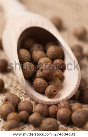Whole allspice pepper super food in a wooden spoon on vintage textile background. Side view close up. - stock photo