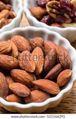 Whole almonds and nuts in bowls at a party table.