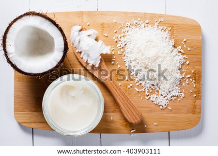 Whole and broken coconut with grated cocont flakes and coconut oil or butter. - stock photo
