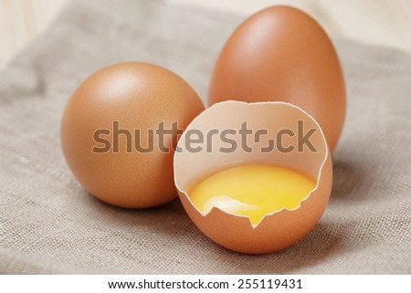 whole and broken raw brown eggs closeup on wood table - stock photo