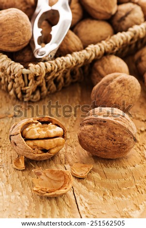 Whole and chopped walnuts on old wooden table - stock photo