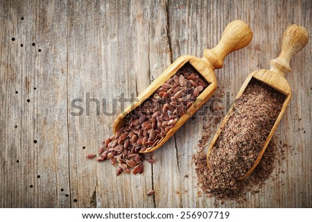 whole and crushed flax seeds on old wooden table - stock photo