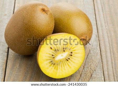 Whole and cut golden kiwifruit/ kiwi (Actinidia chinensis) on wooden cutting board - stock photo
