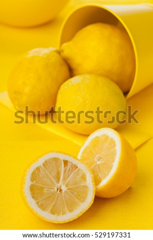 Whole and cut organic lemons on yellow table background