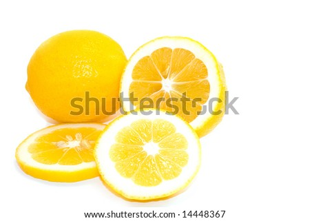 Whole and cut slices of bright yellow meyer lemons on white background.  Space for copy. - stock photo