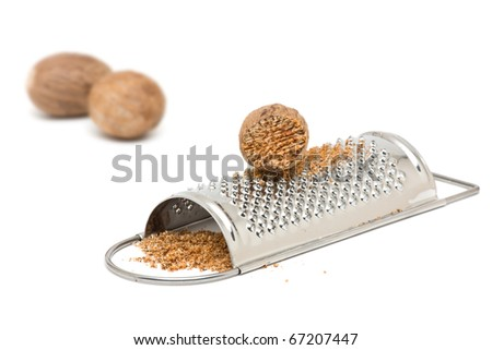 Whole and grind nutmeg with grinder over white background - stock photo