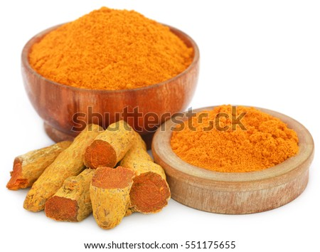 Whole and ground turmeric in bowl, over white background