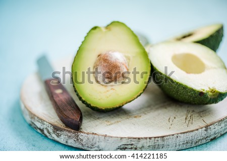 Whole and halved avocado with seed, vibrant pastel colors