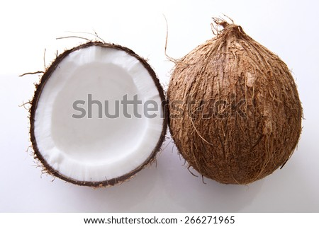 Whole and halved coconuts shot close-up with shallow depth of field. Shot from above on a white background. - stock photo