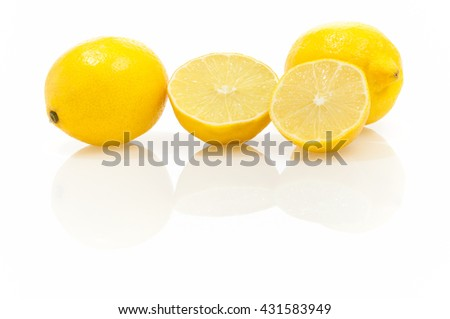 Whole and halved lemons on shiny white background with reflection; Home remedy to prevent colds; Rich in vitamins, Southern fruits - stock photo