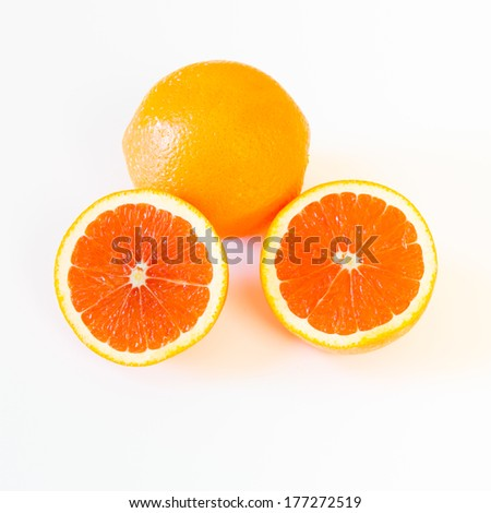 Whole and halved  the cara cara oranges with its pinkish red color interior, on light background - stock photo