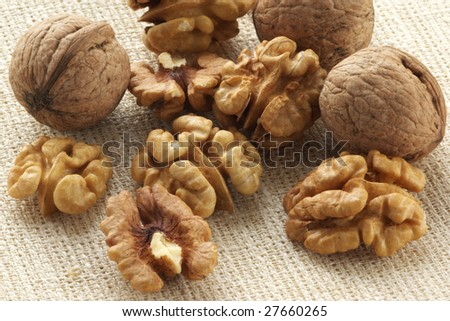 Whole and hulled walnuts on beige linen.