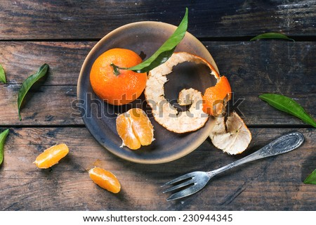 Whole and slice tangerines with leaves on ceramic plate over old wooden table. Top view. - stock photo
