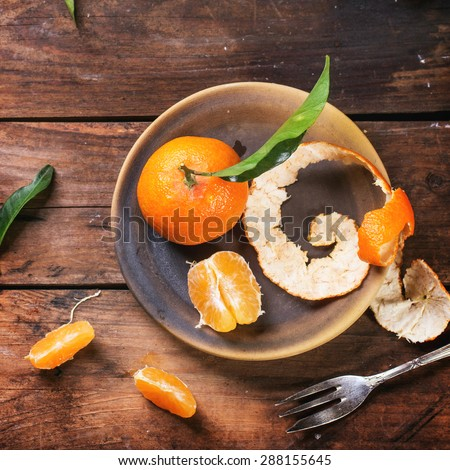 Whole and slice tangerines with leaves on ceramic plate over old wooden table. Top view. Square image. - stock photo