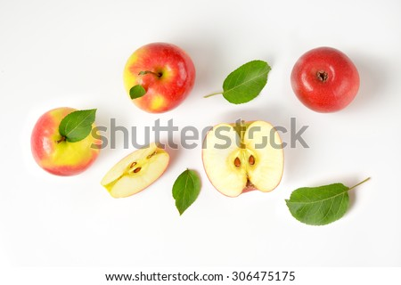 whole and sliced apples with leaves on white background - stock photo