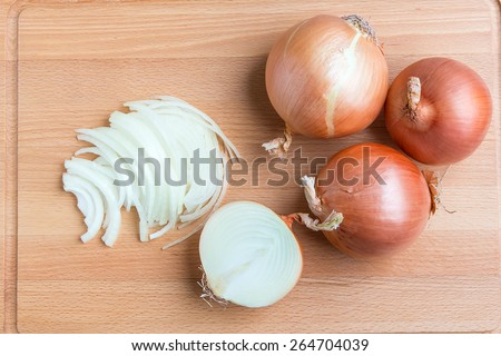 Whole and sliced onions on wooden cutting  board. - stock photo