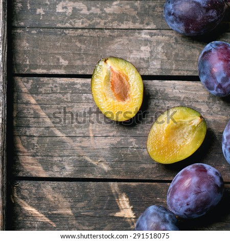 Whole and sliced plums over old wooden table. Top view. Square image - stock photo