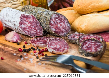 whole and sliced salami with spices and herbs - stock photo