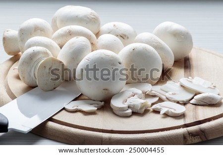 Whole and sliced up champignons on wooden board - stock photo