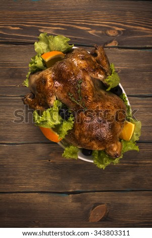 Whole baked chicken with garnish over wooden background. Holidays food. Rustic style. Toned image - stock photo